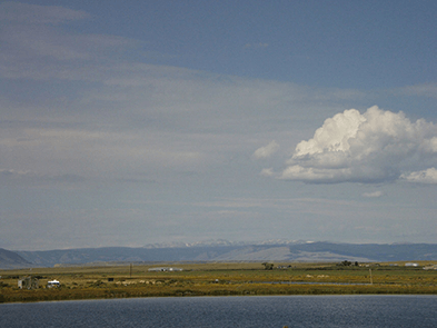 A sparse landscape with mountains in the distance and farmland in the foreground
