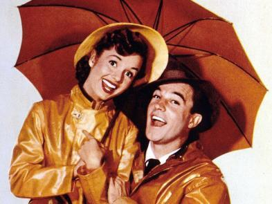 A man and woman stand under an orange umbrella in coats