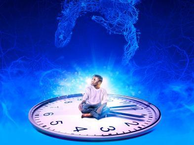 A young boy sits on a clock face surrounded by blue wires.