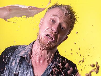 A man appears before a yellow background. He is having chocolate milkshake thrown at his face.