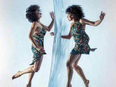 Two identical women float between a veil of water, putting their arms through the water.