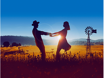 A man and a woman dancing in a field at sunset