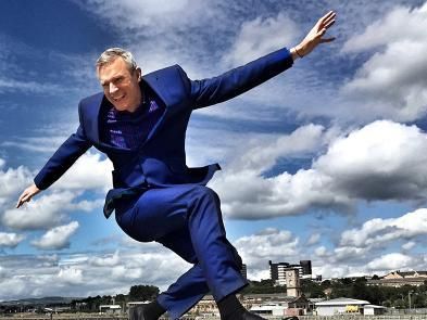 Jeremy Vine jumps in the air, with the blue sky behind him.