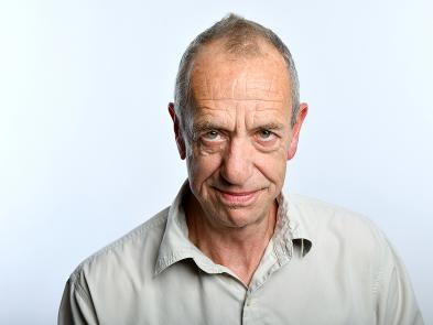 Arthur Smith stands with his head slightly bowed, with a grin on his face, in front of a plain white background.
