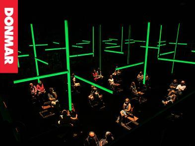 A dark room with green lights. Customers sit in chairs and have headphones on.