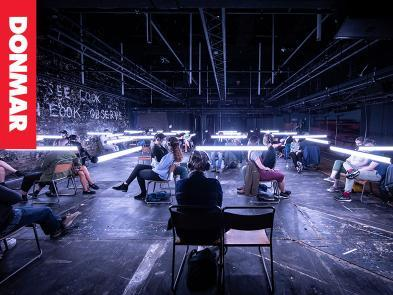 A dark room where people are sat in chairs with headphones on. Lights hang from the ceiling.