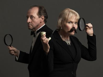 A man and a woman dressed in dark suits hold magnifying glasses and a pipe. The woman has a moutache.
