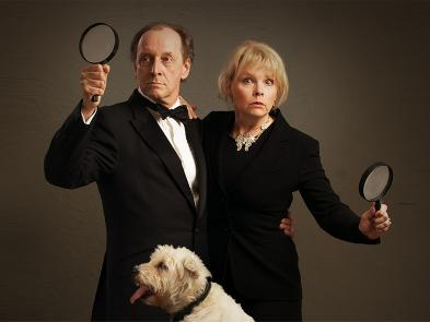 A man and a woman dressed in dark suits hold magnifying glasses and a pipe. A small white dog sits in front of them, completely unawares.